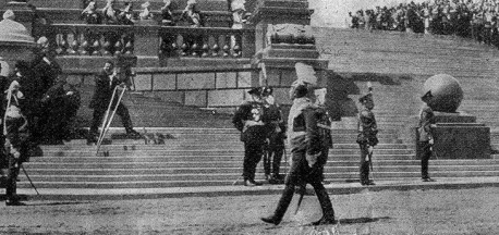 Укрупненный фрагмент другого снимка: хорошо виден человек с камерой на ступенях, можно даже разглядеть, что у него большая залысина и усы.