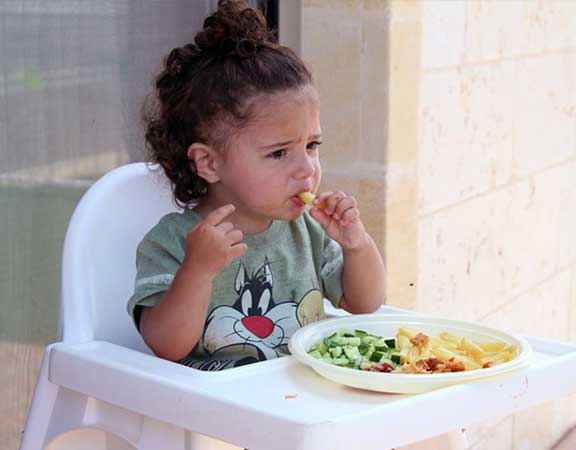 girl-child-in-high-chair-eating-her-veggies