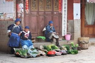 Frauen in Naxi-Tracht verkaufen Gemüse in Baisha