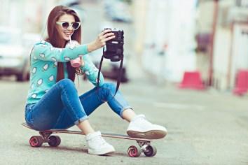 Beautiful young woman posing with a skateboard, fashion lifestyl