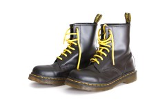 TEL AVIV ISRAEL - SEPT 28 2014: A pair of Doc Martens 8 eyelet 8 inch classic unisex black lace-up fashion combat boots with yellow laces and the sole visible