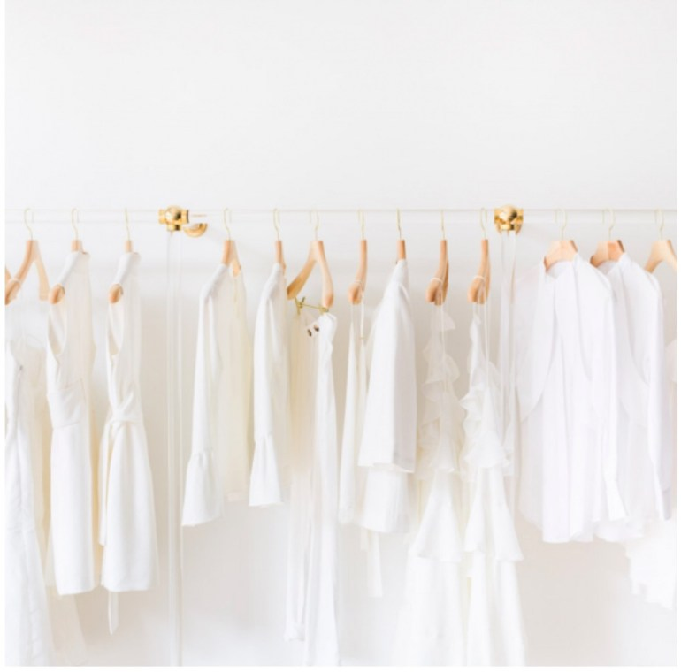 via my domaine all white clothing items on a acrylic rack