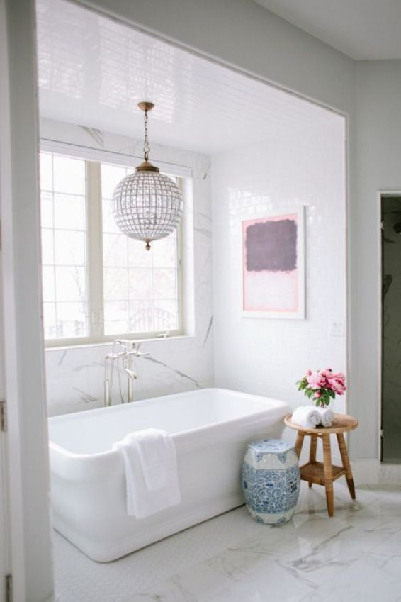 white freestanding soaking tub with ball crystal chandelier and chinese garden stool