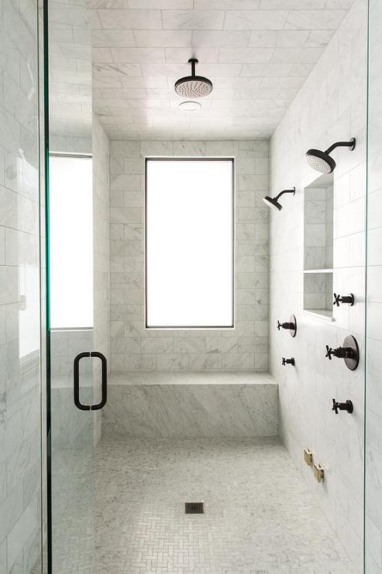 black faucet and shower trim on white marble walk in shower
