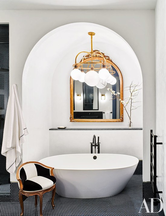 Tub Arched Niche with Freestanding Tub On Black Tile Floor with Gold Mirror and Statement Lighting