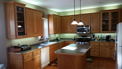 Oak Kitchen Cabinets, Green Laminate Counter Tops, Pendant Island Lighting, Wood Flooring In Kitchen