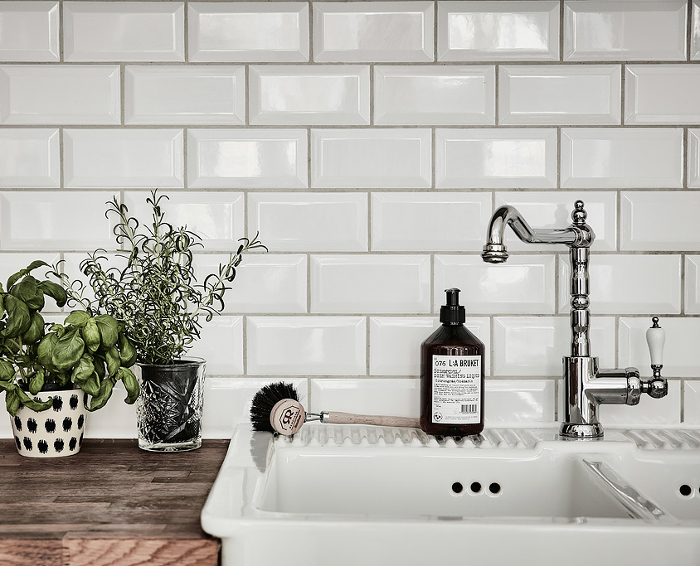 Butcher Block Counter Top, White Porcelain Farmhouse Sink, Beveled 3x6 Subway Tile with Light Gray Grout, Single Arm Chrome Faucet with White China Handle