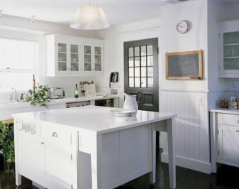 white kitchen with bead board, black door, chalkboard, large island with mission legs