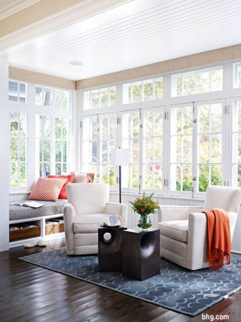 Pair of Neutral Swivel Chairs on Blue Geometric Rug with Orange Throw and Dark Wood End Tables In Sunroom with Transom Windows