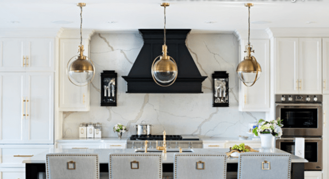 Houzz Kitchen with Black Wood Hood, Full Calcutta Marble Back Splash, Gold Pendant Lighting, White Shaker Style Cabinets with Brass and Acrylic Hardware, Gray Bar Stools with Nail Heads