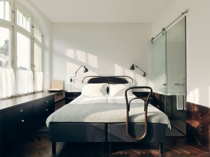 Sunny hotel room with gray upholstered bed with fluffy white bedding and armed wall sconces, lace curtains at the windows filter sunlight- via remodelista