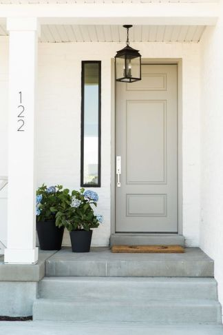 A smokey warm brown grey is a nice companions to the black accents of this white house.-via pinterest