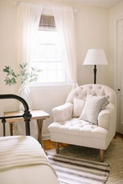 Creamy tone on tone guest room with tufted upholstered chair, floor lamp, iron bed-pinterest
