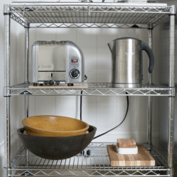 Chrome wire 3 tiered shelf with toaster, electric kettle, french press, dark and medium wood mixing bowls, wood butcher block cutting board with stack of small white appetizer plates on it