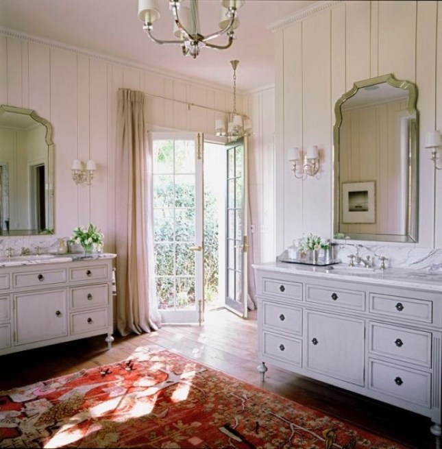 Traditional Bath with dual white furniture style vanities, red persian area rug with sunlight streaming in - via simon 140