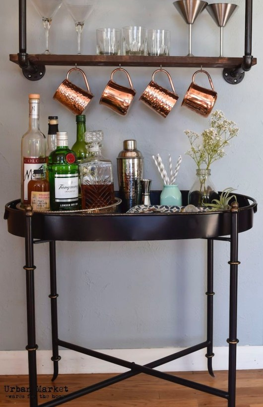 urban market black tray table with industrial pipe shelf above with moscow mule copper mugs