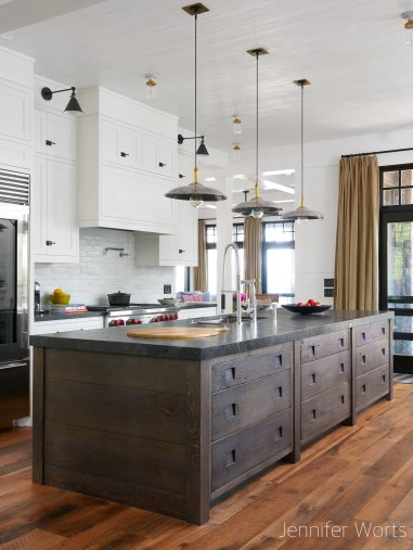 transitional kitchen with mixed white recessed door cabinets and walnut drawer cabinets for island, dark honed stone counter tops, industrial pendant lighting over island, burlap drapes at large dark frame doors to patio