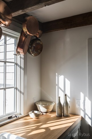 Greta Rybus Kitchen With Rustic Wood Beam Ceiling, Farmhouse Sink, Copper Pots Hanging From Ceiling and Wood Counter Tops