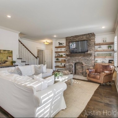 Family Room with sisal area rug, white slip covered sofa's, worn leather chair in front of stone fireplace with slab wood mantle, creamy white walls and walnut wood floors