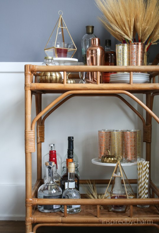 inspiredlycharm rattan bar cart in natural color with cake stand with highball glasses, glass of stripped straws and dessert plates