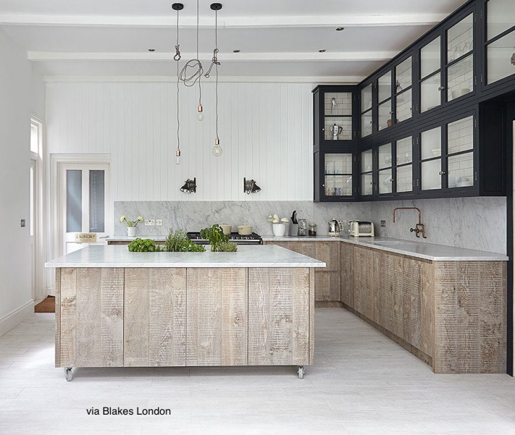 - washed worn wood base cabinets in white kitchen, upper cabinets black framed with glass doors, white marble counter tops with full splash, vertical wood slat walls painted white, flooring is dusty light tile, herbs on island counter, lighting over island is mesh of tangled black cords and open light bulbs