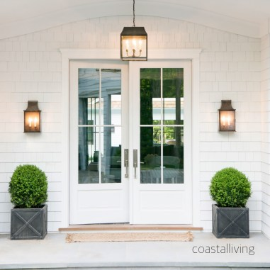A bright white pair of doors is the perfect entrance to this coastal home. via coastal living