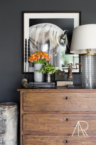 Chest with White horse Art on Gray Wall, silver lamp and white vase with orange tulips