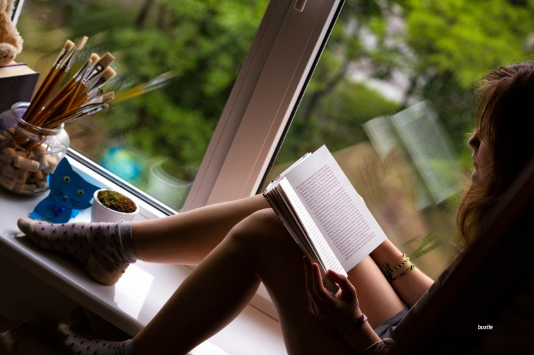 teen girl sitting on a windowsill reading a book in last sunlight of the day - via bustle
