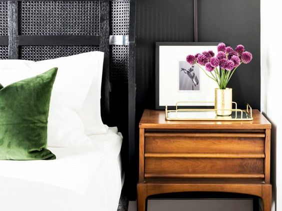 from mydomaine bedroom with wood nightstand, gray woven headboard brass and mirror tray