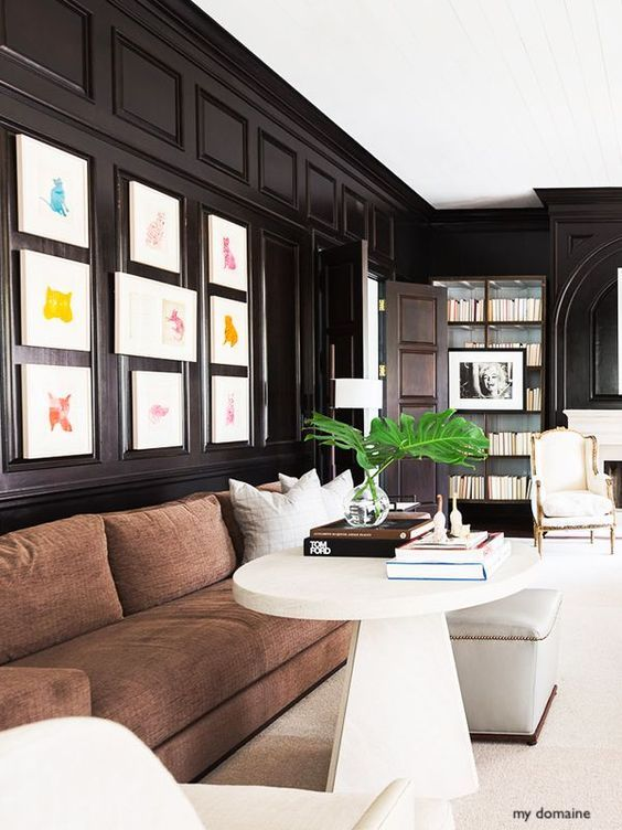 my domaine Dark Wood Paneled Modern Library with White Matted Colorful Art-Sofa Just Begging for A Throw To Curl up With