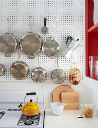 white pegboard with stainless pots/pans and nearby red open shelf