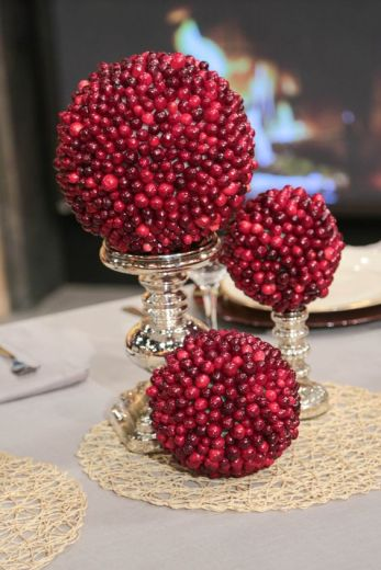 christmas decorations of cranberry topiaries on mercury glass candlesticks