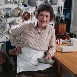 Julia Child in kitchen with white pegboard