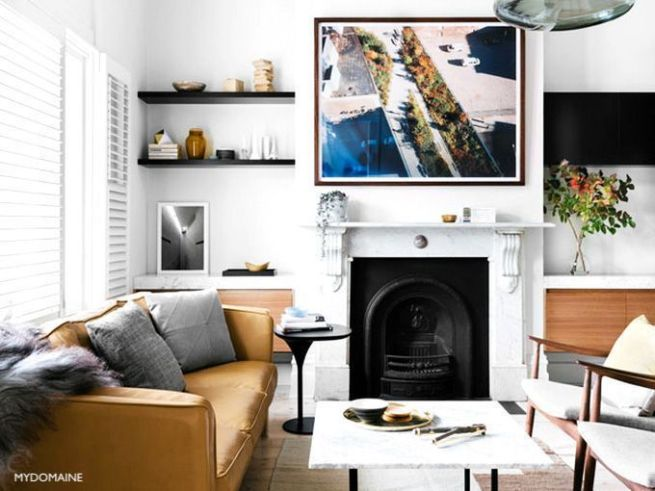 mydomaine Architectural Fireplace -wood tables-camel sofa- large art over fireplace- open shelves -marble table