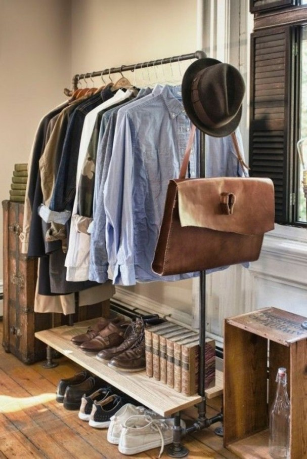casual-business-attire-clothes-rack-with-male-clothes-pale-blue-shirts-blazers-brown-shoes-sneakers-big-bag-felt-hat-books-wooden-furniture