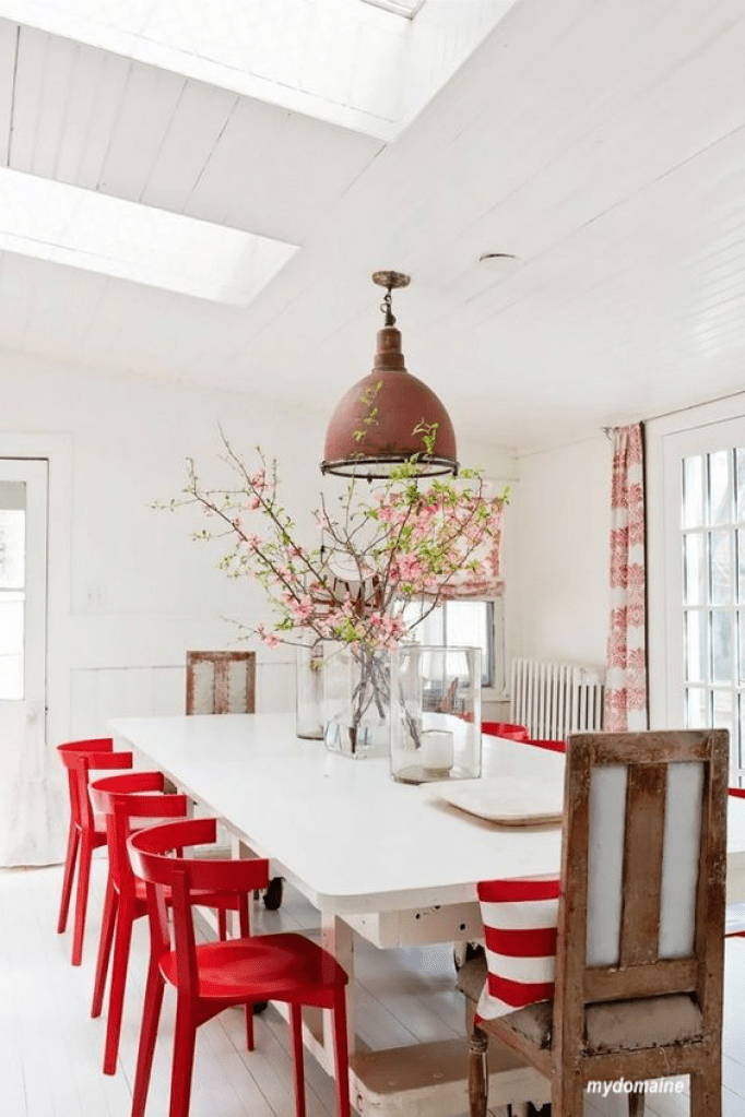 mydomaine white table with red chairs, stripped pillows and floral curtains