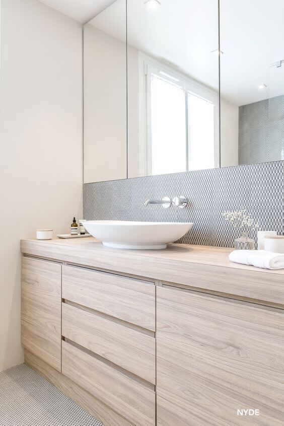 NYDE Bathroom Design-Light Stained Cabinets-White Vessel Bowl - Small Pattern Tile Tall Backsplash-Wall Mounted Faucet