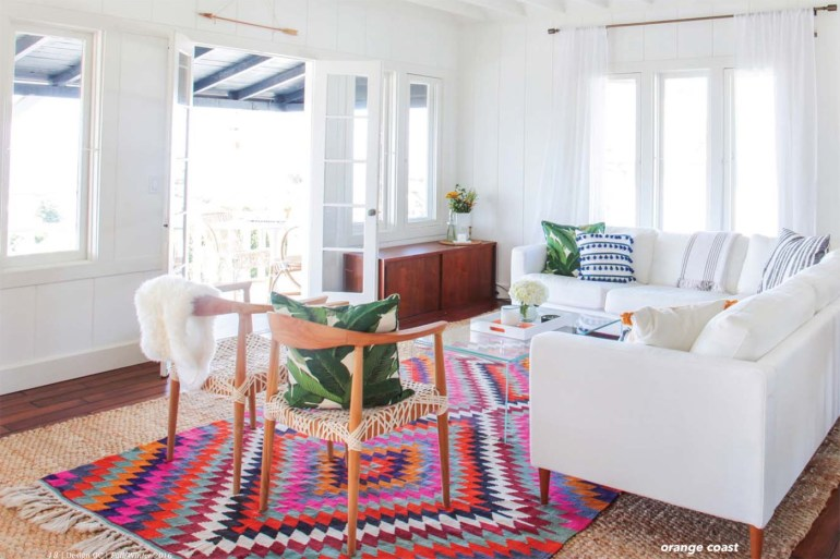 orange coast living room- colorful area rug-white sofas-white drape panels- white walls-wood arm chairs -console cabinet