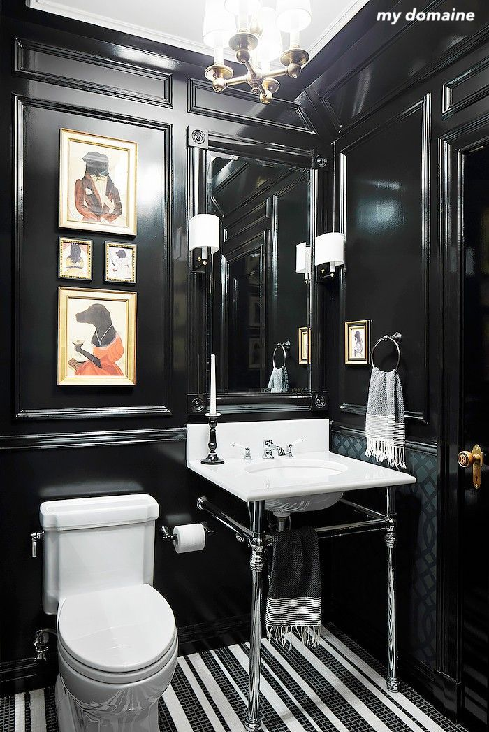 mydomaine black and white powder room- striped tile floor-chrome pedestal sink- black paneled walls- mirror sconces