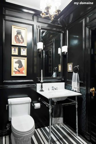 mydomaine black and white powder room- striped tile floor-chrome pedestal sink- black paneled walls- mirror sconces