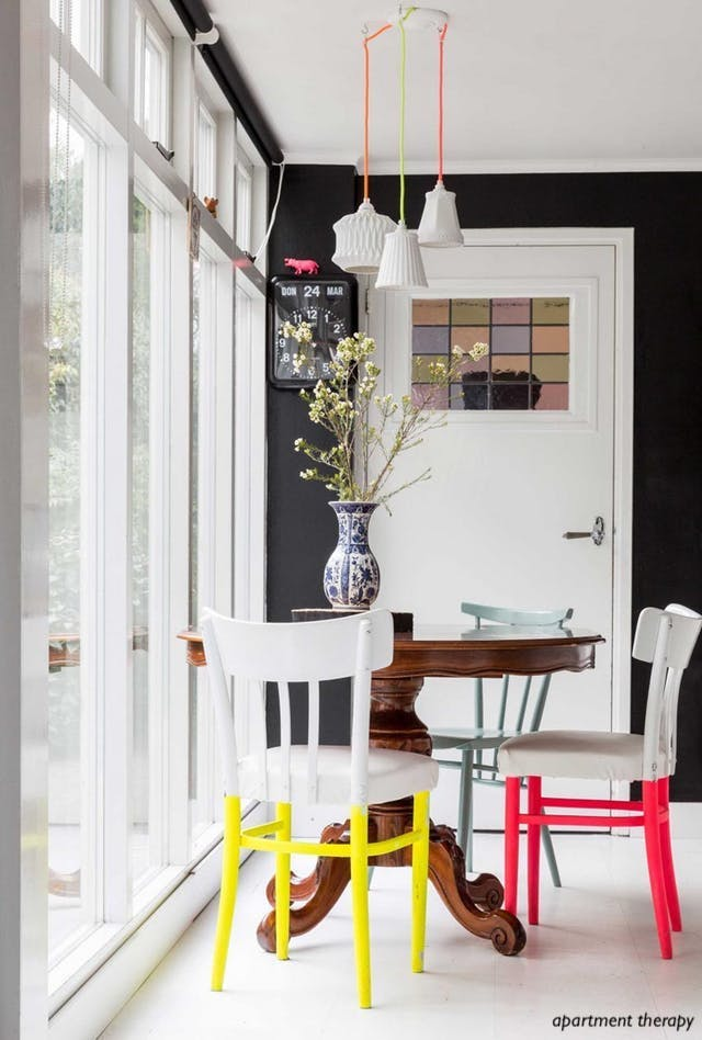 apartment therapy breakfast nook-colorful chairs- pedestal table-black walls