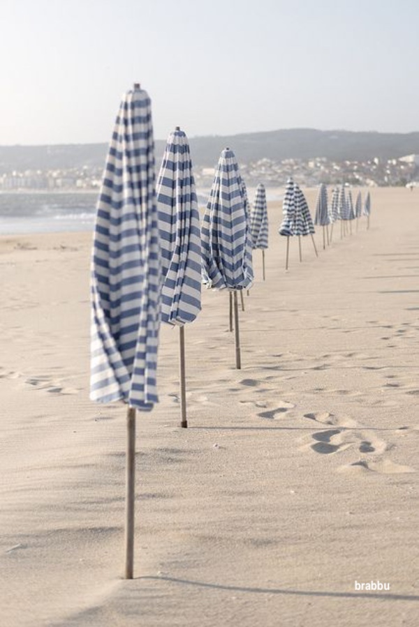 brabbu blue and white stripped beach umbrellas in sand