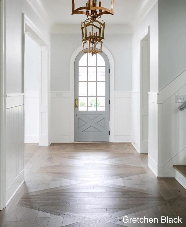 gretchen black- foyer- gray arch door- patterned wood floor- gold statement lighting-wood wall panels