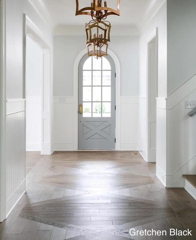 gretchen black- foyer- gray arch door- patterned wood floor- gold statement lighting-wood wall panels