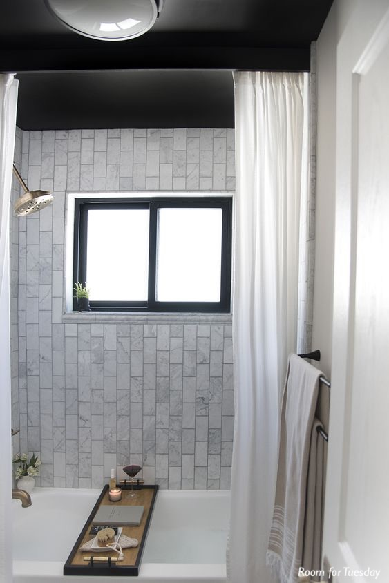 room for tuesday-alcove shower-marble subway tile-black ceilings-tub caddy-soaking tub-shower curtain