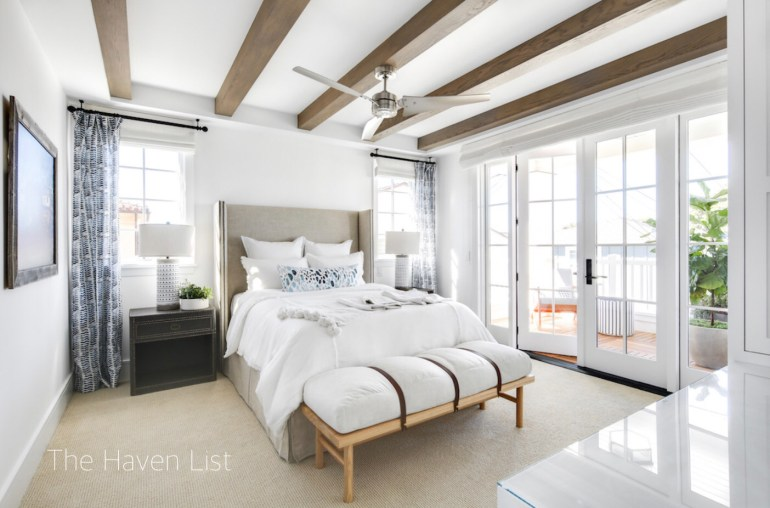 the haven list-summer-bedroom-blue-drapes-ceiling beams-sisal carpet-french doors-upholstered headboard