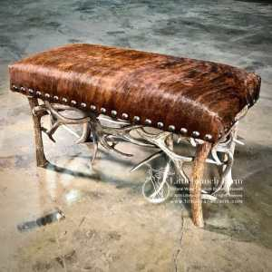 Rustic bench with antler sheds and cowhide