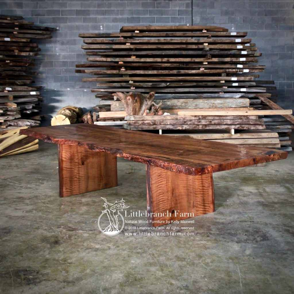 Large curly redwood dining table in warehouse of wood.