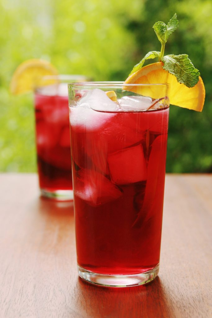 Cranberry juice or punch with fresh orange slice on a table outside