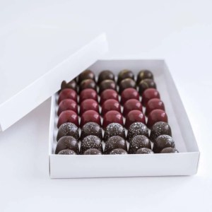 an open catering box of chocolate pralines with red and speckled white theme